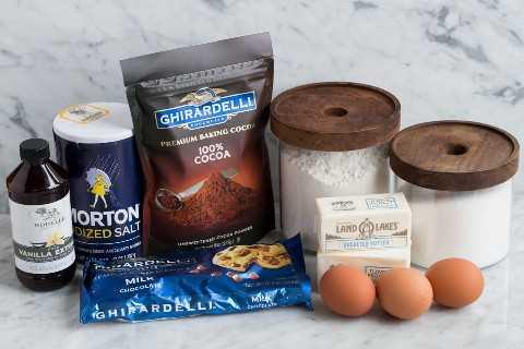 Los ingredientes necesarios para hacer los brownies que se muestran aquí incluyen harina, azúcar, huevos, mantequilla, cacao en polvo, sal, vainilla y chispas de chocolate.