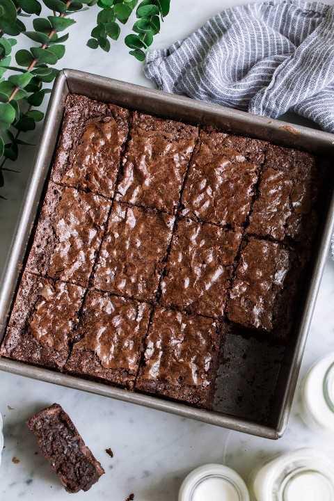 Imagen de arriba de cuadrados de brownie cortados en una fuente para hornear cuadrada.