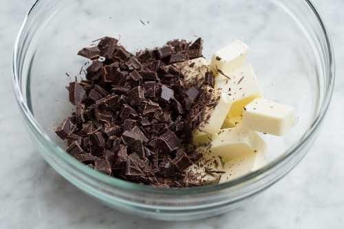 Muestra cómo hacer un pastel de chocolate sin harina, agregando chocolate picado y mantequilla a un tazón de vidrio.