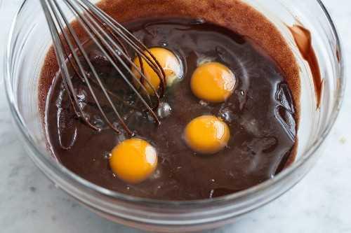 Batir los huevos en una mezcla de pastel de chocolate sin harina en un tazón.