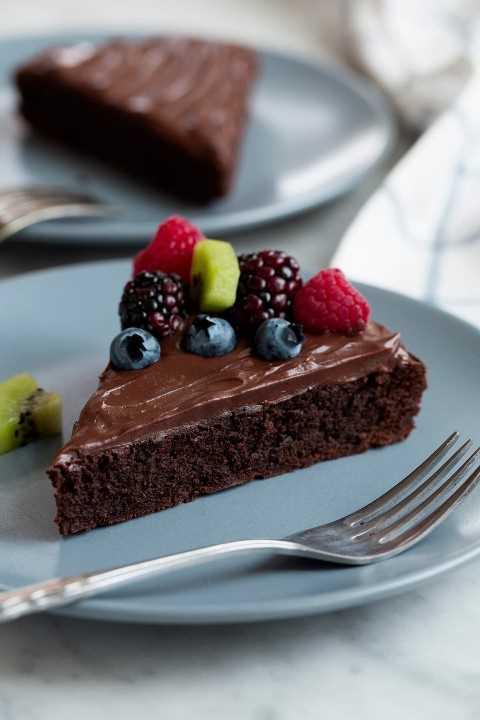 Pastel de chocolate sin harina en un plato azul. El pastel está cubierto con ganache y fruta fresca.