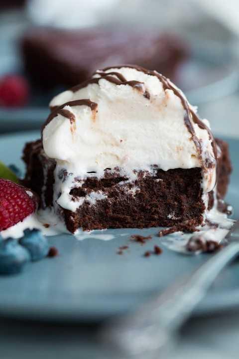 Pastel de chocolate sin harina con varios bocados comidos para mostrar. Está cubierto con helado y salsa de chocolate.