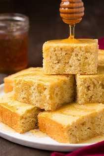 Rociando miel sobre una pila de pan de maíz en un plato blanco sobre una mesa de madera.