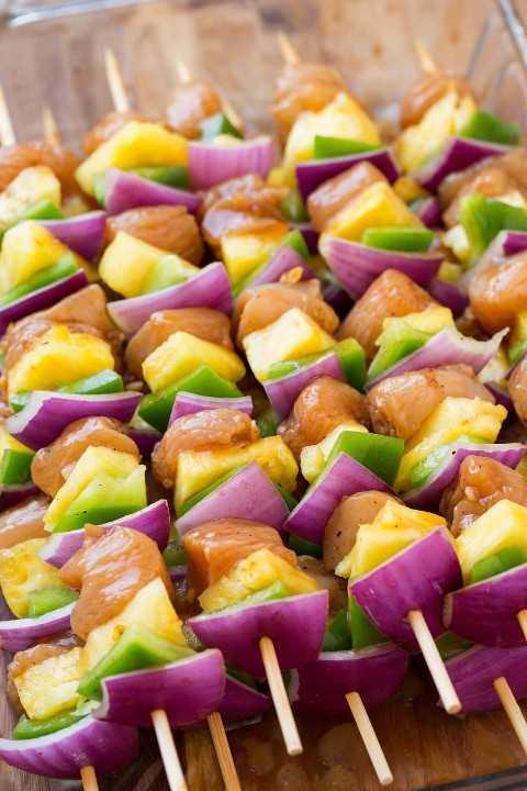 Brochetas de pollo con pimiento rojo cebolla y piña. Se muestra antes de cocinar.