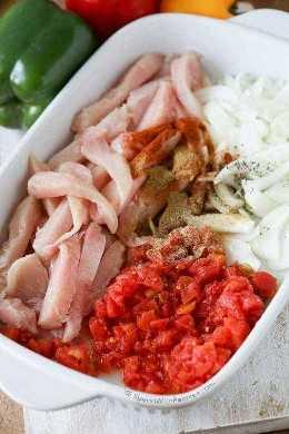 Ingredientes para fajitas de horno preparadas en una cacerola que incluye tomates y cebollas de pollo