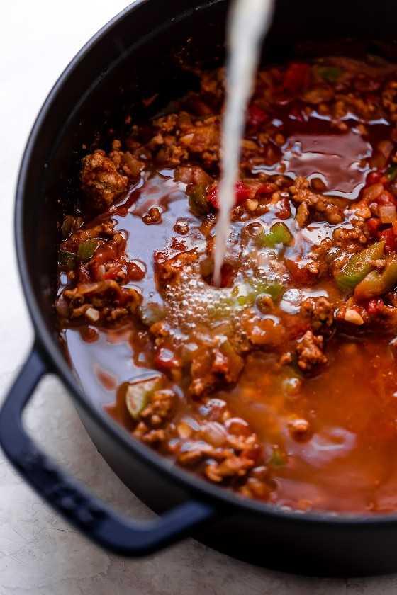 Mostrando cómo hacer chile de pavo. Verter el caldo en la mezcla en la olla.