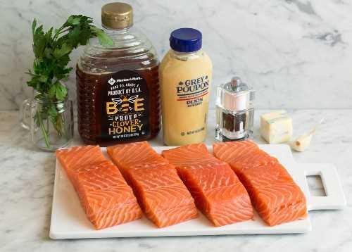 Los ingredientes para el salmón al horno se muestran aquí. Filetes de salmón miel dijon mostaza ajo sal pimienta perejil.