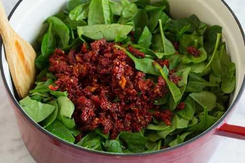tomates secos picados al sol y espinacas frescas en una olla grande