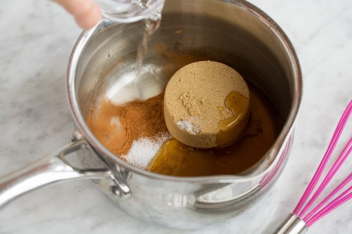 Misture o açúcar mascavo, o mel, a canela, o sal e a água em uma panela para fazer uma camada de granola.