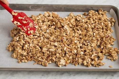 Extienda la mezcla de granola en una bandeja para hornear forrada con papel pergamino para hornear.