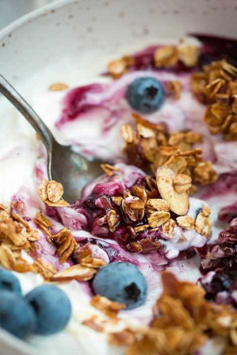 Cerrar imagen de granola con yogur, bayas y salsa de arándanos.