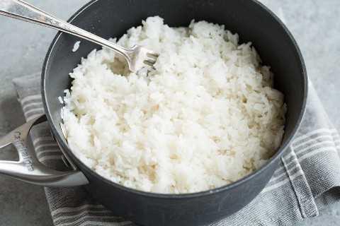 Fluffing terminó el arroz de coco en una cacerola con un tenedor.