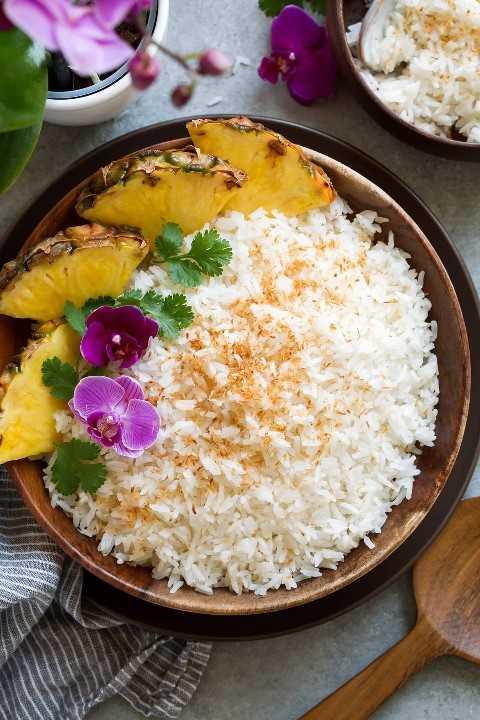 Cuenco de madera lleno de arroz de coco cubierto con flores, cilantro y un lado de piña fresca.