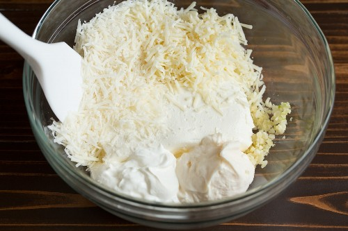 Mezcle el queso crema, la mayonesa, la crema agria, el ajo y los quesos rallados en un tazón para hacer salsa de alcachofa y espinacas.