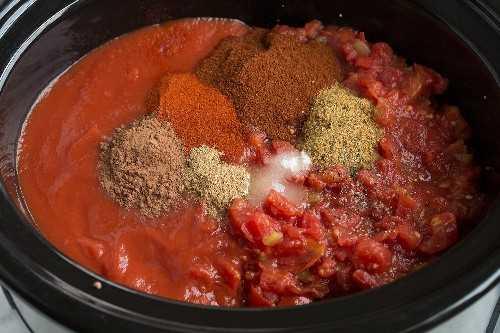 Agregue tomates, salsa de tomate y especias a la olla de cocción lenta para el chile.