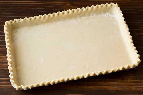 Corteza de pastel para tarta de manzana en una bandeja para hornear con borde antes de agregar el relleno.