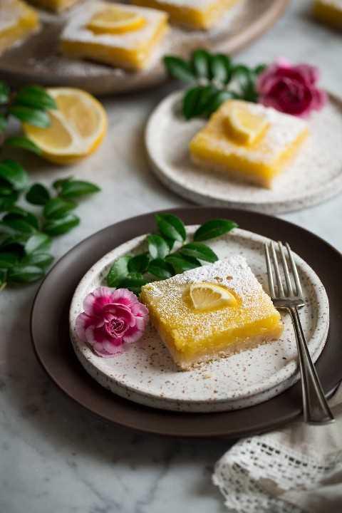 Barras de limón o dos platos de postre decorados con flores y verduras.