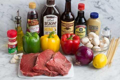 Los ingredientes necesarios para hacer los kebabs de carne que se muestran aquí incluyen filetes, pimientos, cebolla roja, ajo, limón, mostaza dijon, salsa de soja, Worcestershire, miel, vinagre de vino tinto, aceite de oliva, ajo en polvo.