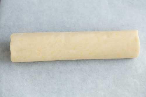 Mostrando cómo hacer galletas de mantequilla de limón. Balanceo de masa en un tronco.
