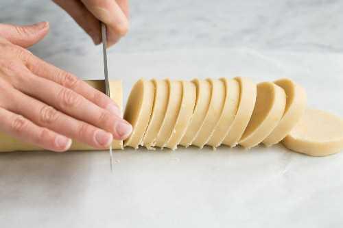 Mostrando cómo hacer galletas de mantequilla de limón. Cortar troncos en rodajas.