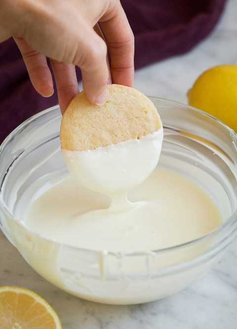 Sumergir las galletas de mantequilla de limón en chocolate blanco derretido.