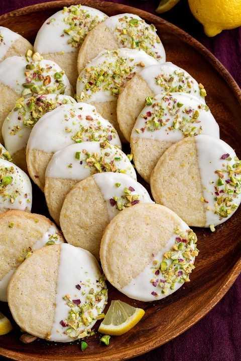 Galletas de mantequilla en una placa de madera para servir. Con sabor a limón, chocolate blanco y pistachos.