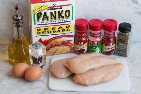 Los ingredientes necesarios para hacer nuggets de pollo que se muestran aquí incluyen pechugas de pollo, panko, tomillo, pimentón, ajo en polvo, pimienta de cayena, huevos y aceite de oliva.