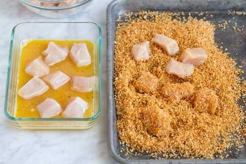 Mostrando cómo hacer nuggets de pollo. Mezcle los trozos de pollo con el huevo y luego vístelos con la mezcla de pan rallado sobre una bandeja para hornear.