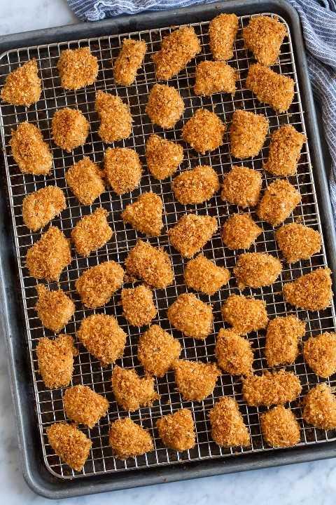 Nuggets de pollo mostrados en una rejilla de alambre sobre una bandeja para hornear después de hornear.