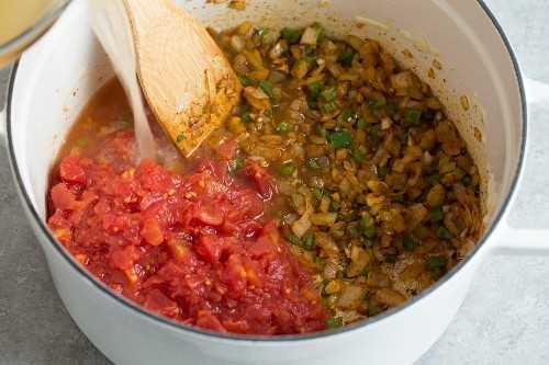 Mostrando cómo hacer pollo posole. Saltear las verduras, agregar caldo y tomates.
