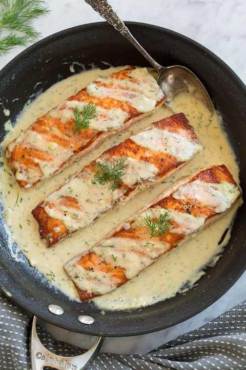 Tres filetes de salmón en una sartén con una cremosa salsa dijon.
