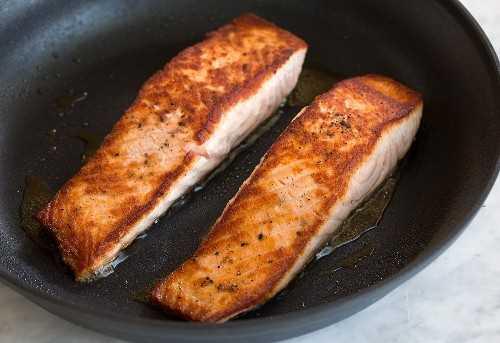 Dos filetes de salmón dorado a la sartén marrón se muestran aquí en una sartén antiadherente grande.