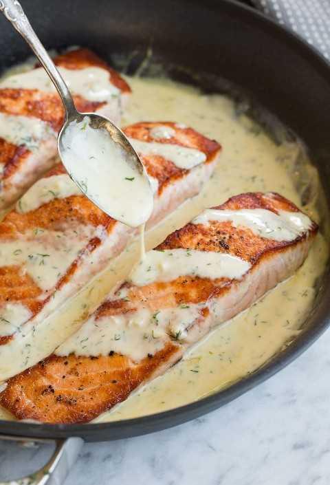 Cuchara de salsa sobre un filete de salmón en una sartén.