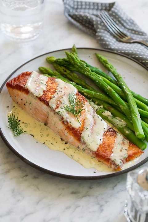 Filete de salmón en un plato blanco sobre una superficie de mármol. Cubierto con salsa de dijon y servido con un lado de espárragos.