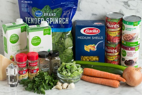 Os ingredientes mostrados aqui incluem cenoura, cebola, aipo, abobrinha, feijão, alho, salsa, manjericão, orégano, parmesão, caldo de legumes, espinafre, casca de macarrão, tomate enlatado e feijão.