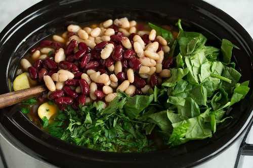 Adicione o feijão, espinafre e salsa ao minestrone.