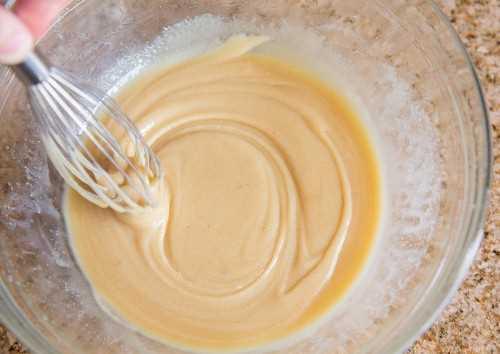 Mostrando como fazer caramelo. Bata a manteiga, xarope de milho, leite condensado, sal e açúcar em uma tigela de vidro.