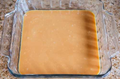 A mistura de caramelo é despejada em uma assadeira de vidro com manteiga.