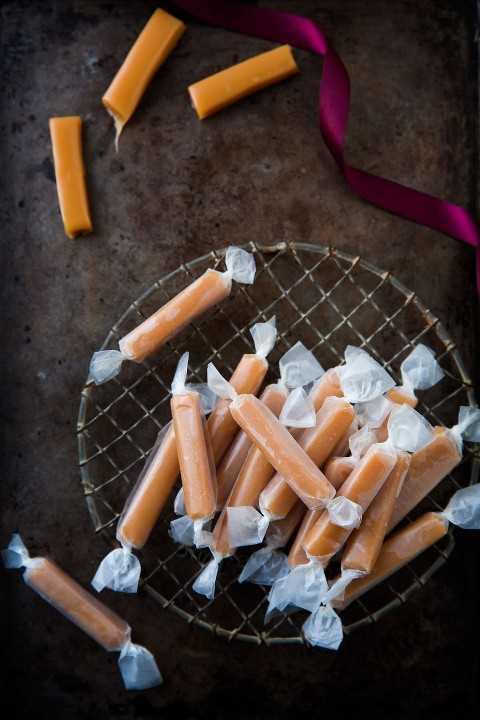 Pilha de doces embrulhados em papel de cera com vários doces desembrulhados cortados de um lado.