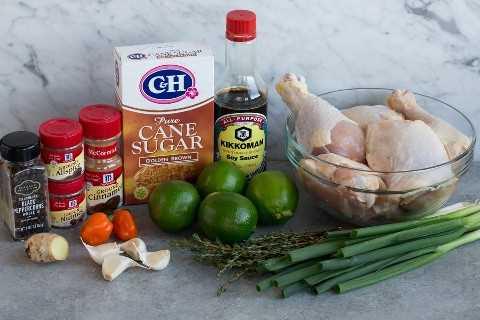 Ingredientes de Jerk Chicken que se muestran aquí, incluidos trozos de pollo, cebollas verdes, tomillo, limas, salsa de soja, azúcar morena, canela, pimienta de Jamaica, nuez moscada, pimienta, pimienta de gorro escocés, ajo y jengibre fresco.