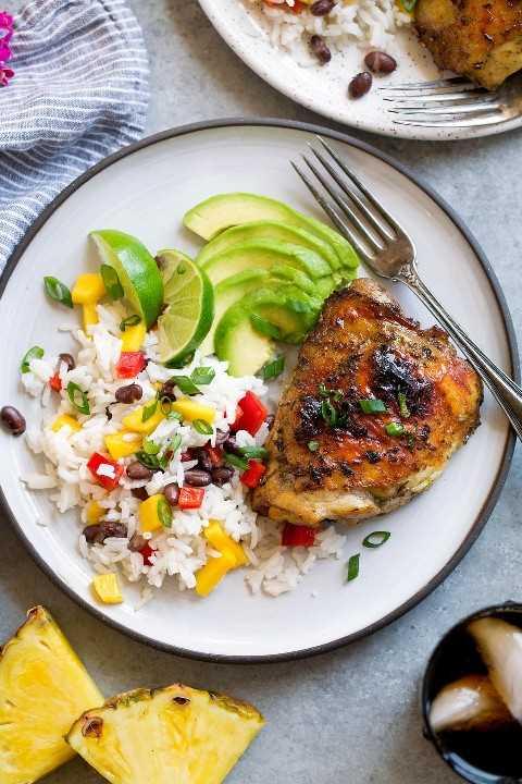 Una pieza de pollo a la brasa con arroz y aguacate.
