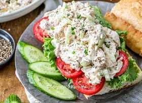 Ensalada clásica de pollo con mayonesa sobre un rollo cubierto con tomate y lechuga