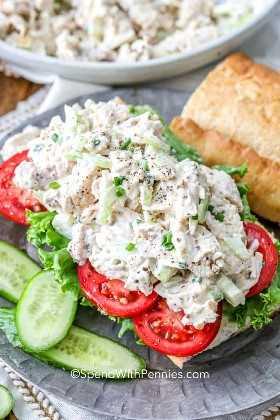 Clásico sándwich de ensalada de pollo en una baguette sobre tomates servidos con pepinos.