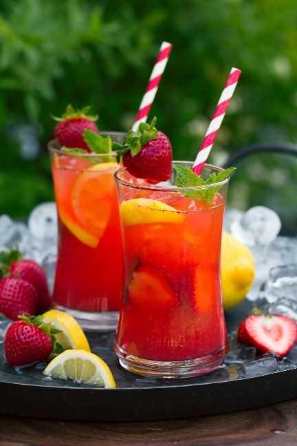 dos vasos de limonada de fresa en bandeja con rodajas de limón y fresas frescas