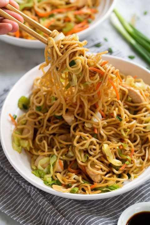 Tirando chow mein com pauzinhos.