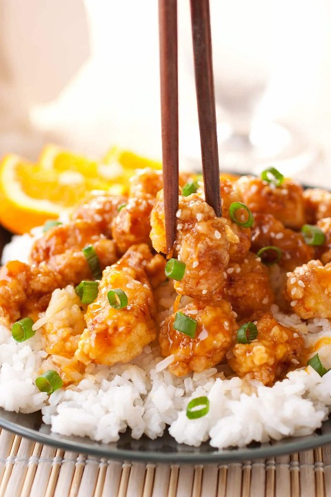 Foto cercana de pollo a la naranja china con palillos agarrando una pieza de pollo