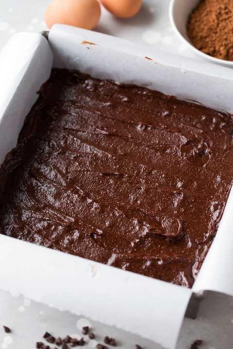 masa de brownie saludable en una sartén con papel pergamino