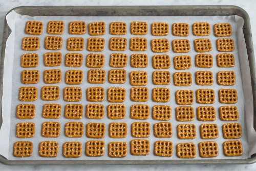 Mostrando cómo hacer un regalo navideño fácil. Poner pretzels cuadrados alineados en filas en una bandeja para hornear forrada de papel pergamino.