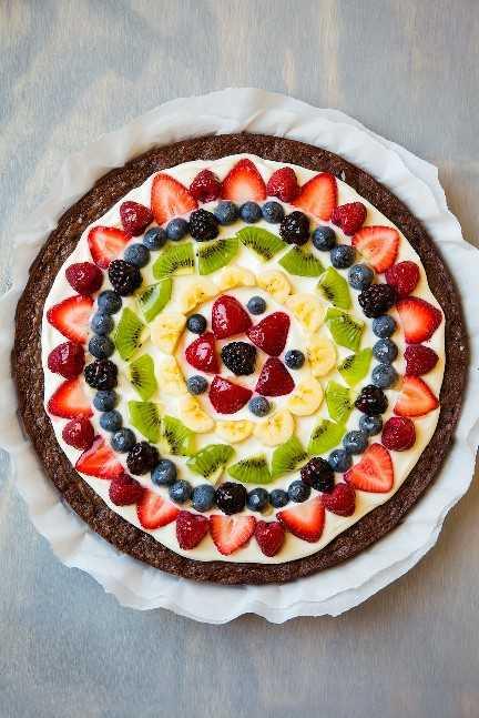 Brownie Fruit Pizza con glaseado de queso crema, fresas, frambuesas, arándanos, moras, kiwi y plátanos.