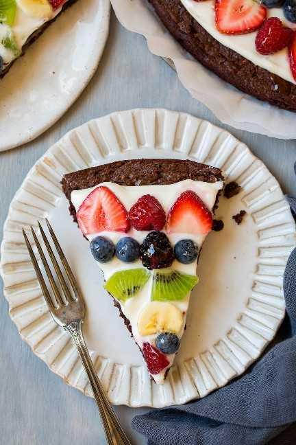 Brownie fruta pizza rebanada en un plato blanco, sentado sobre una superficie de madera azul.